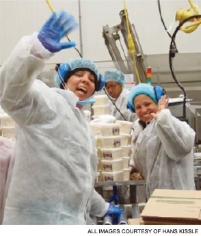 Cheerful employees at work at Hans Kissle on a salad production line.